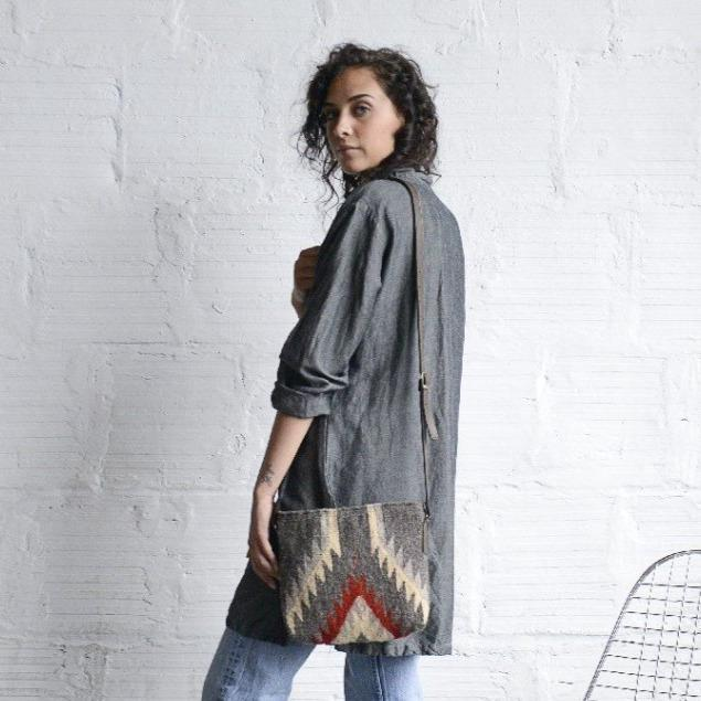Woman Holding Wool Crossbody Purse Featuring Zapotec Diamond Design In Beige And Red On Gray With Brown Leather Strap