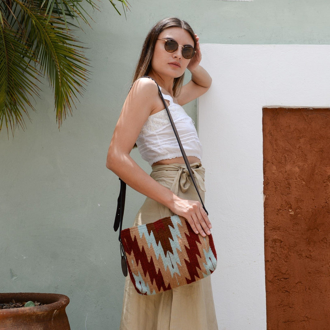 Woman Modeling Wool Crossbody Purse Featuring Zapotec Lightning Design In Burgundy, Sage Green, Tan And Soft Peach With Brown Leather Strap