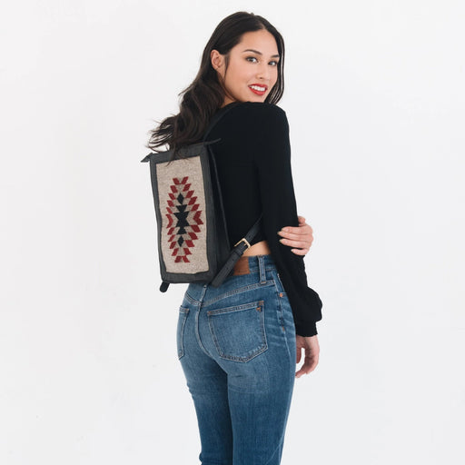 Woman Wearing Leather And Wool Backpack Featuring Woven Zapotec Diamond Design In Red And Black On Gray With Black Leather