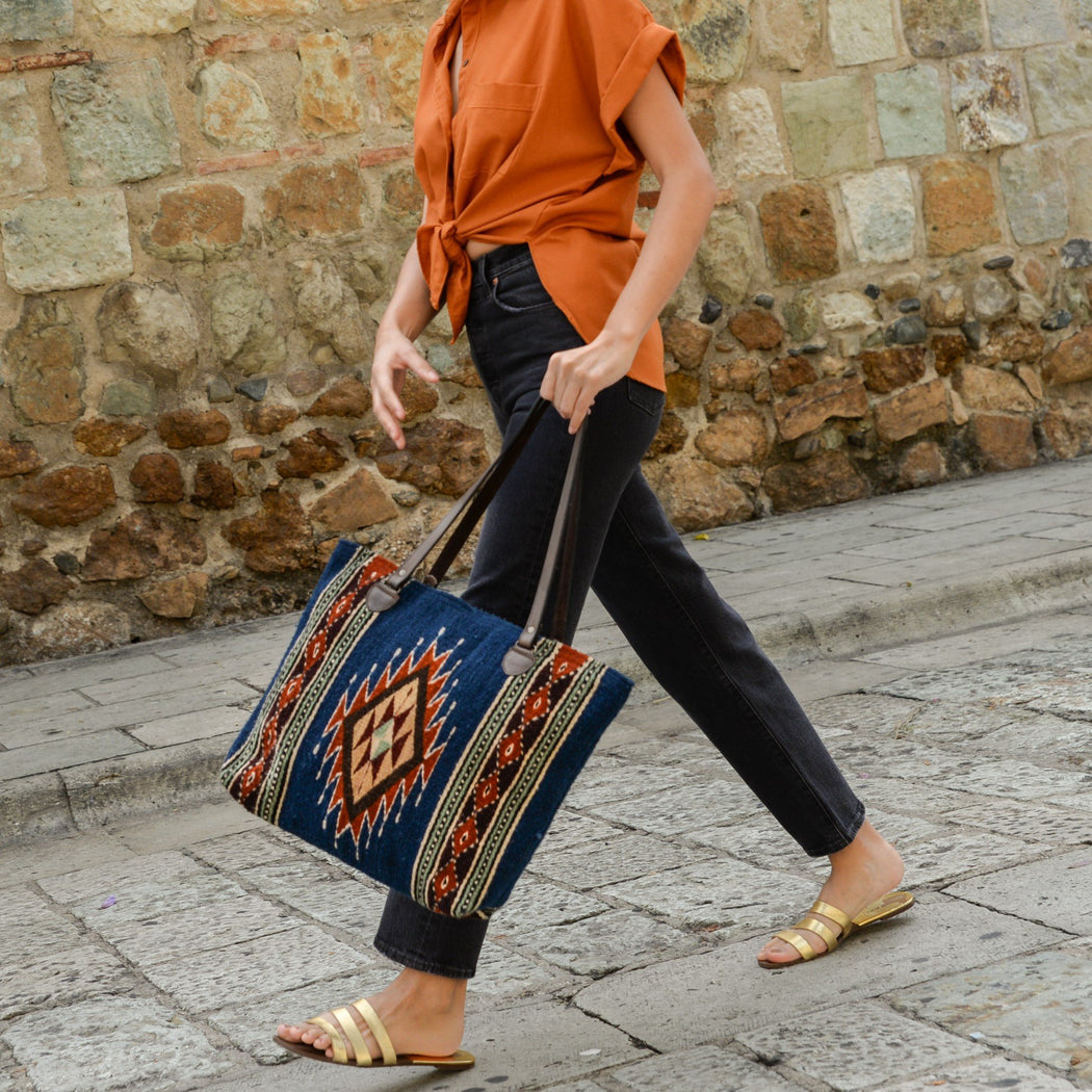 Close Up Of Woman Walking With Wool Tote Bag Featuring Blue And Orange Zapotec Design With Brown Leather Handles