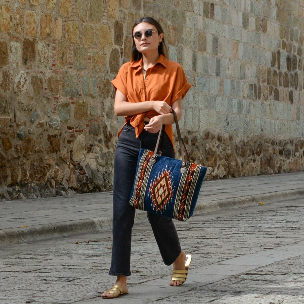 Woman Walking With Blue Wool Tote Bag Featuring Zapotec Diamond Design In Orange With Brown Leather Handles