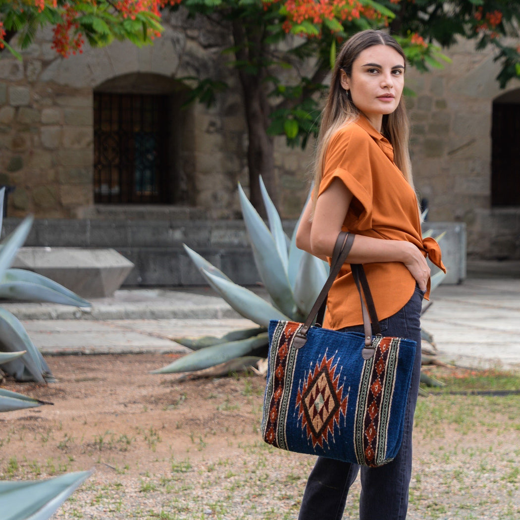 Woman Looking Over Shoulder Holding Wool Tote Bag Featuring Zapotec Diamond Design In Orange On Blue With Brown Leather Handles