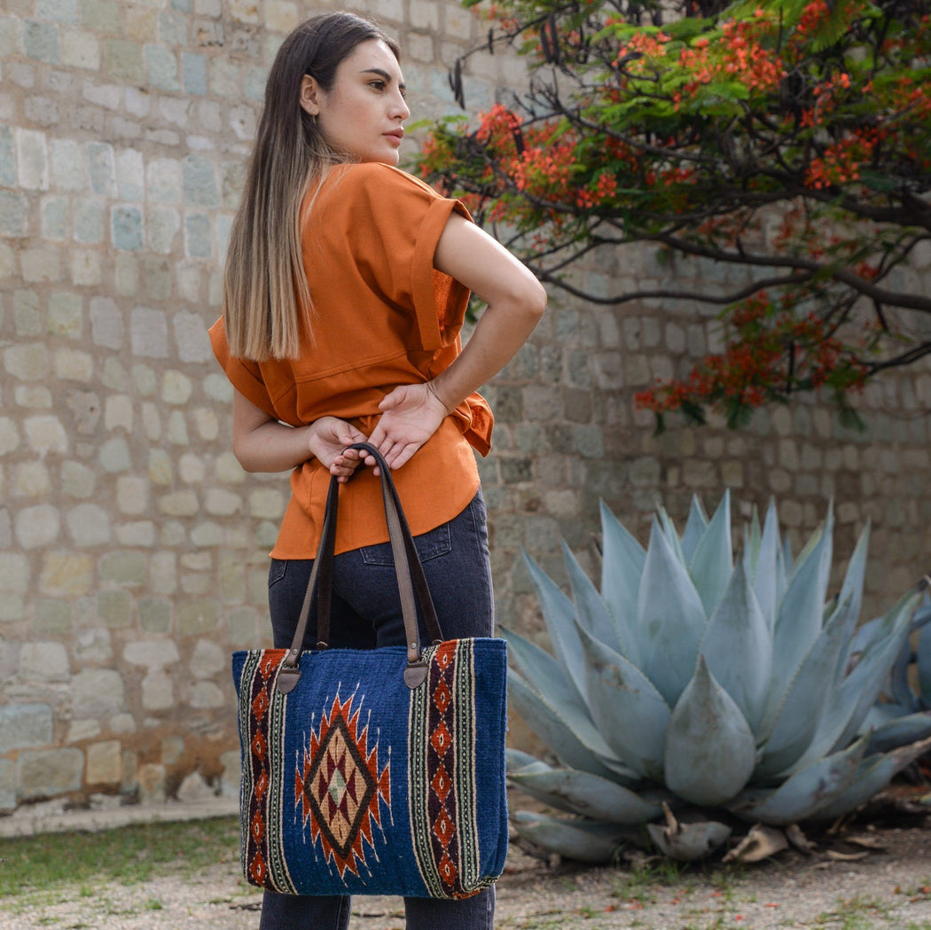 Woman Holding Blue Wool Tote Bag Featuring Orange Zapotec Diamond Design With Brown Leather Handles Behind Her Back