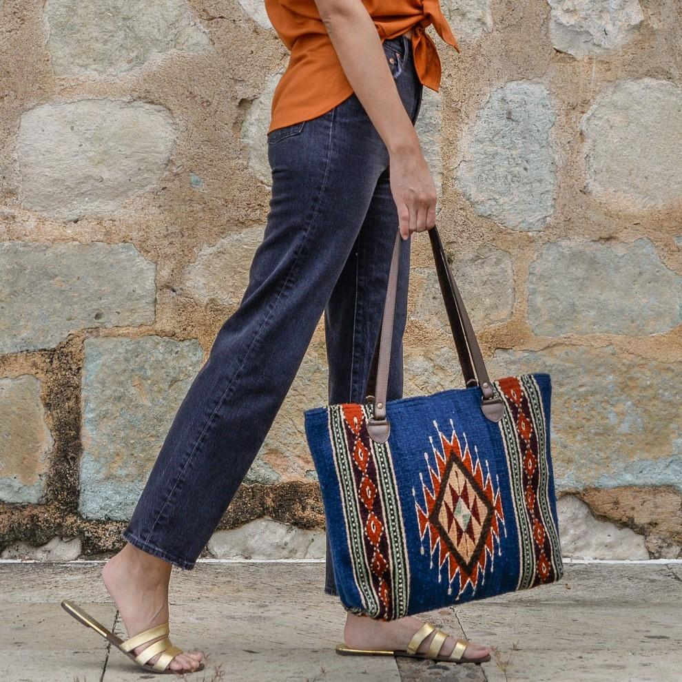 Close Up Of Woman Holding Wool Tote Bag In Blue Featuring Orange Zapotec Lightning Designs With Brown Leather Handles