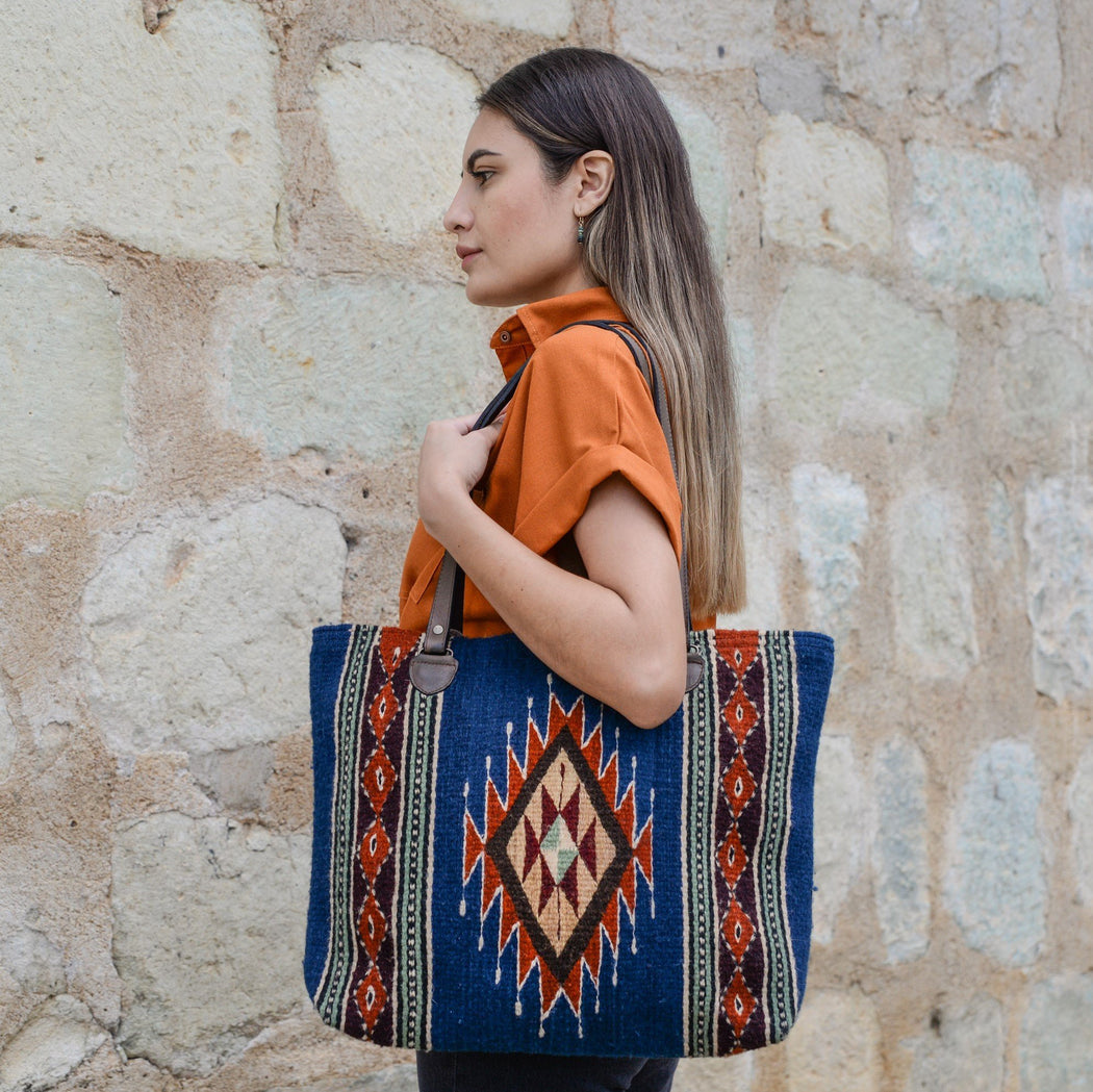 Woman Holding Blue Wool Tote Bag Featuring Zapotec Diamond Design In Rust Orange With Brown Leather Straps