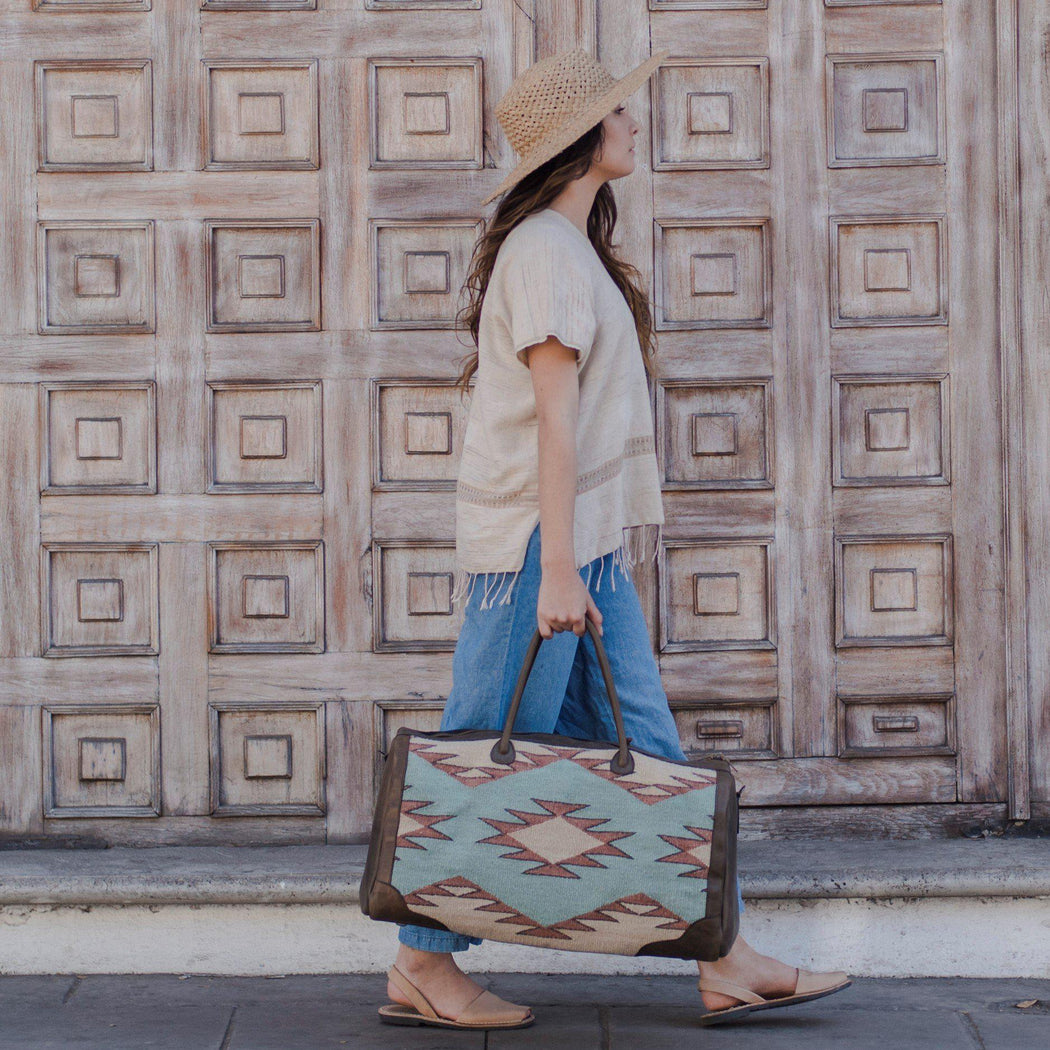 Woman Walking With Wool And Leather Duffel Bag Featuring Zapotec Diamond Design in Beige, Orange And Mint Green with Brown Leather Sides and Handle