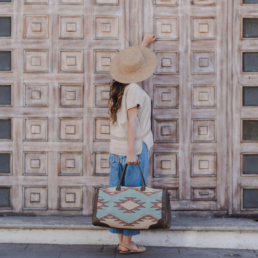 Woman Knocking on Door Holding Leather and Wool Duffel Bag Featuring Zapotec Diamond Design in Mint Green, Orange and Beige with Leather Handles and Sides