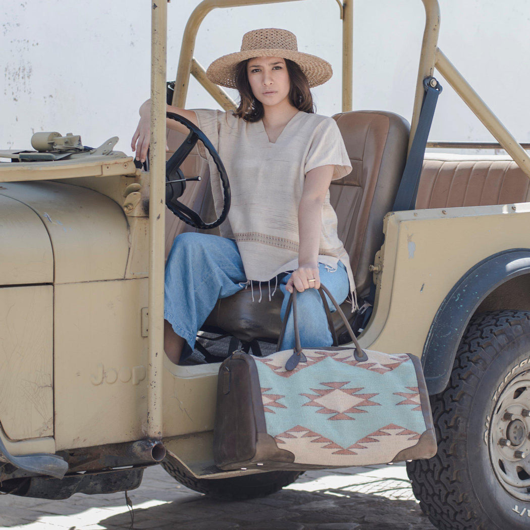 Woman Sitting in Jeep Holding Leather and Wool Duffel Bag Featuring Woven Zapotec Diamond Design in Beige, Orange and Mint Green