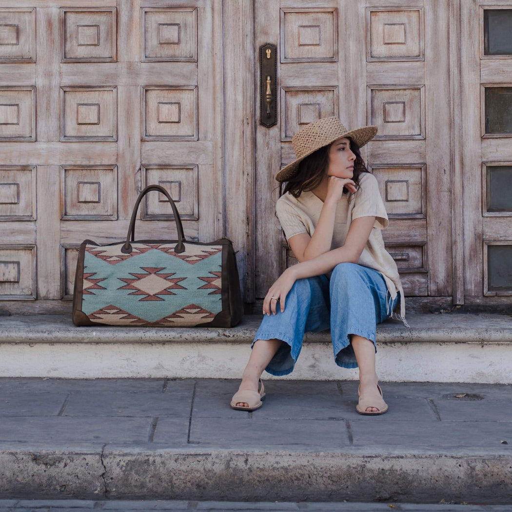 Woman Sitting on Steps Next to Leather and Wool Duffel Bag Featuring Zapotec Diamond Design in Beige and Mint Green with Brown Leather