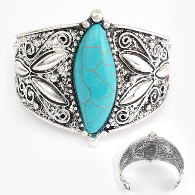 Silver cuff bracelet with detailed raised design and turquoise stone