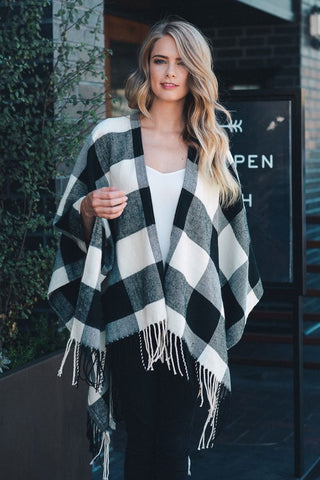 Front view of women wearing black & white checked poncho with tassels