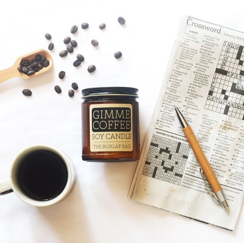 Gimmie Coffee Candle pictured with a cup of coffee and cross word puzzel