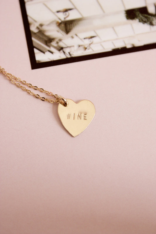 Mini gold heart charm necklace hand stamped with the word wine