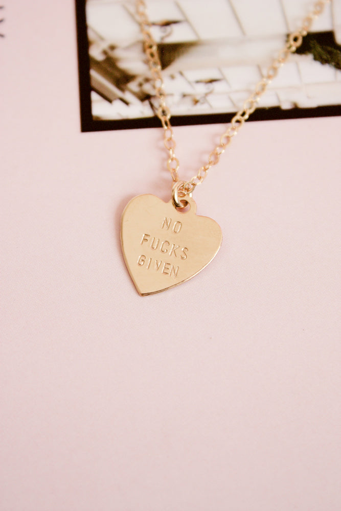 Gold heart charm necklace hand stamped with the words No Fucks Given
