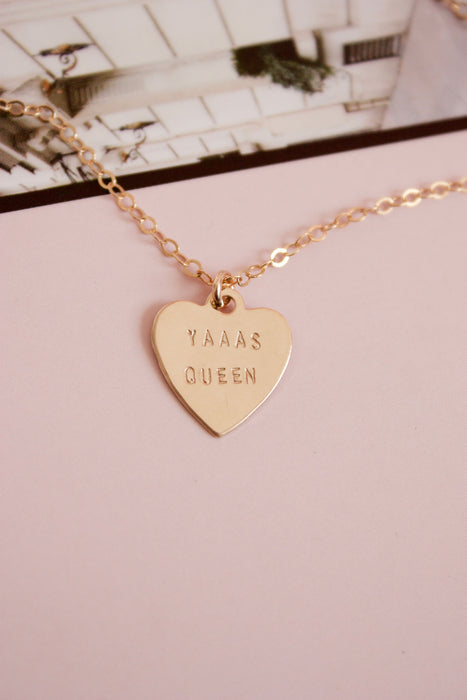 Gold heart charm necklace hand stamped with the words Yaaas Queen