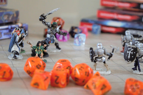 A game of Dungeons & Dragons being played, with orange dice and painted metal miniatures on a vinyl battle mat.