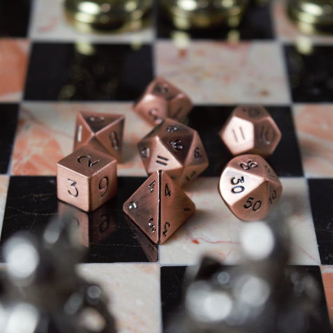 Copper DnD dice set on a chess board