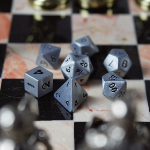 Miniature DnD dice set made out of metal with an antique silver finish