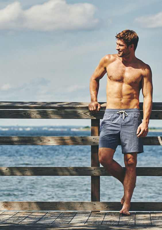 man in swim trunks on pier