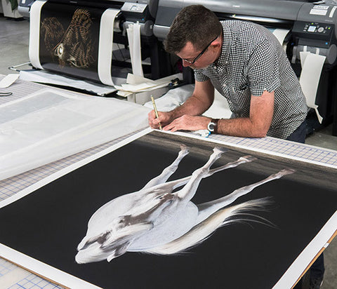 Signing a custom large scale photographic print prior to framing and shipping.