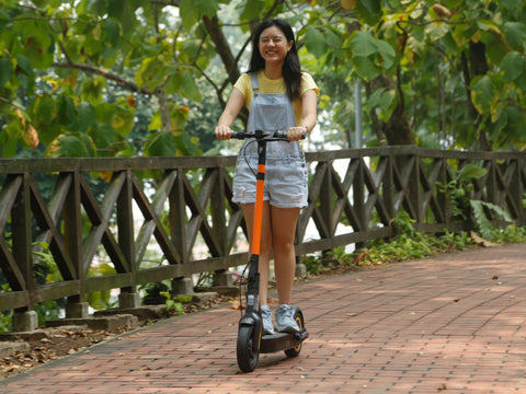 a girl rides down a pathway on a segway MAX