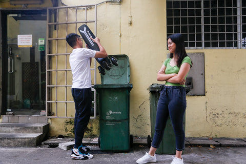 a boy tries to throw a non-certified e-scooter into the rubbish bin, while a girl looks on disapprovingly