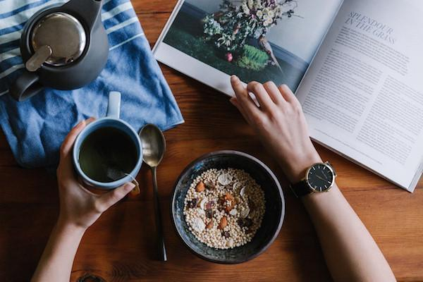 Someone's hands holding coffee, a magazine, cereal