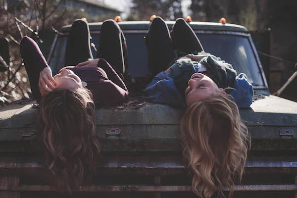 Two ladies laying on the hood of truck