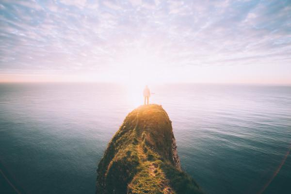 Man standing on cliff overlooking the ocean at sunset