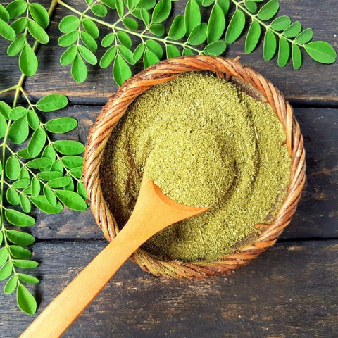 Scooping moringa leaf powder and moringa leaves