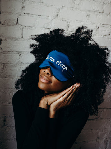Girl with curly hair wearing silk sleeping eye mask