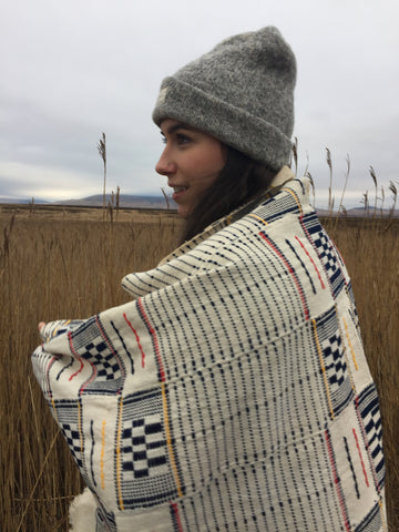 Girl in grey beanie and woven blanket in field