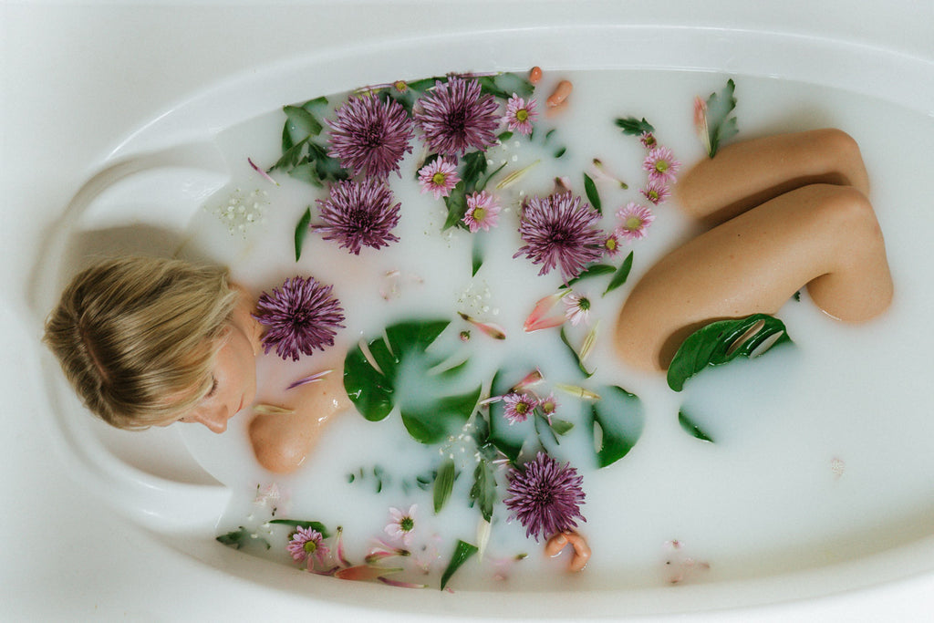 Girl relaxing in bath with flowers and plants