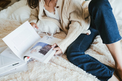 Girl in cardigan and jeans browsing magazine on bed