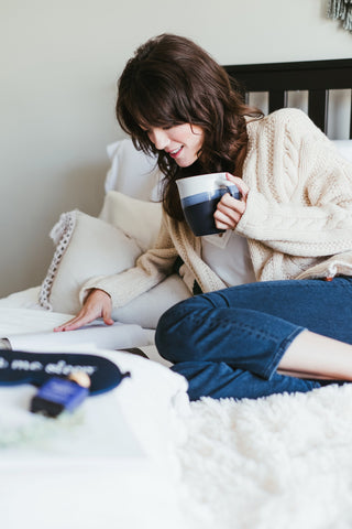 Lady reading magazine on bed with mug of hot chocolate