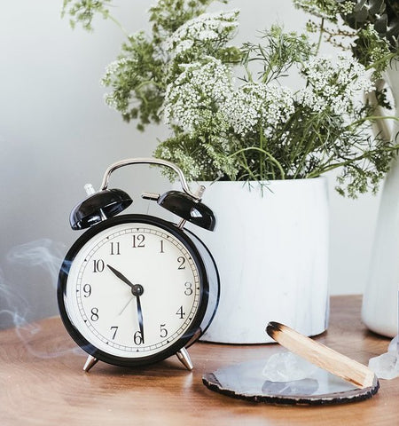Bedside table with alarm clock, incense, baby's breath flowers