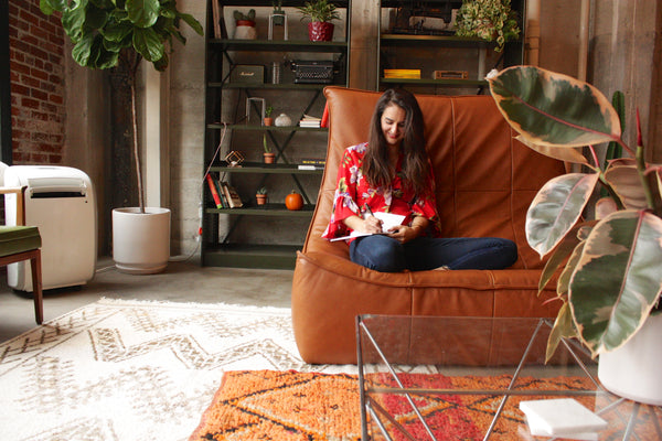 Kasey Dreier sitting on brown couch writing in journal