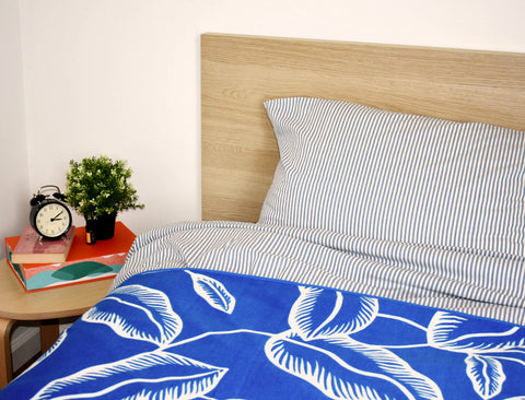 Bed and bedside table with alarm clock and plant
