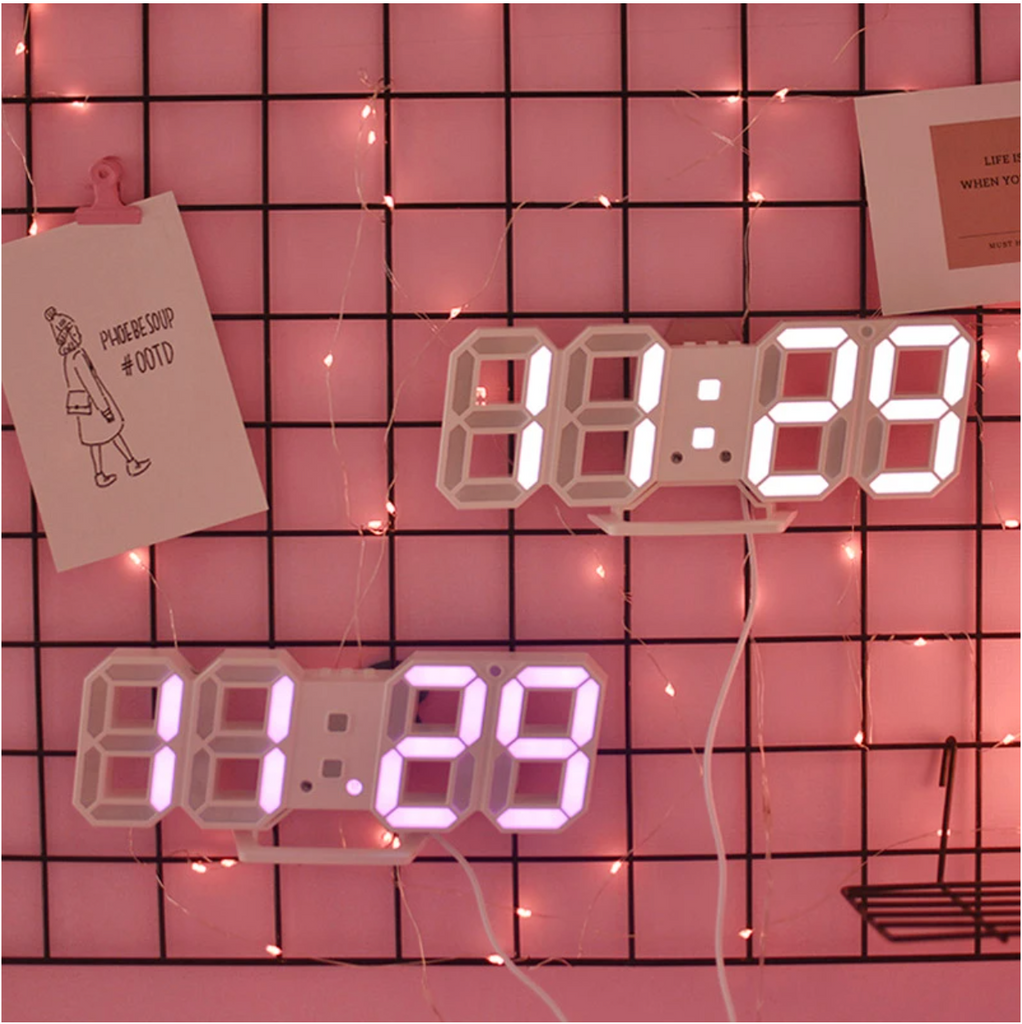 Numbers of a clock displayed on pink wall.