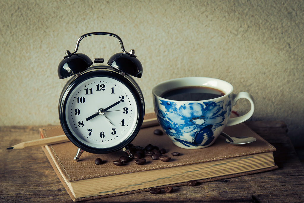 analog alarm clock next to coffee in mug with blue flower sitting on top of book