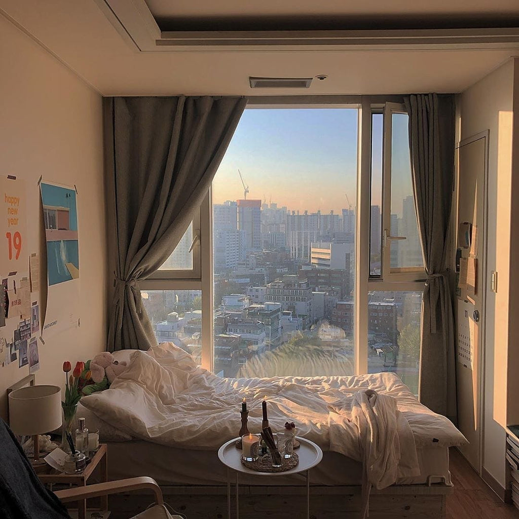 Bedroom with large window and grey curtains overlooking a cityscape.