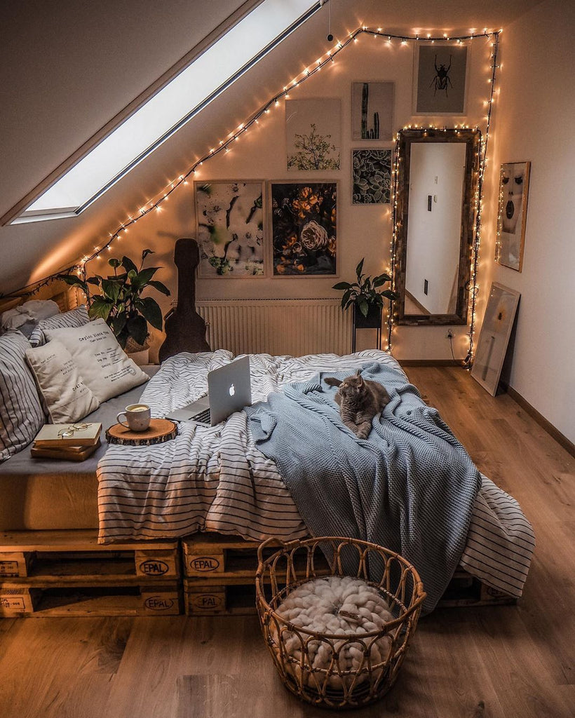 Overview of bedroom with fairy lights, bed with striped sheets, books, and a grey cat.