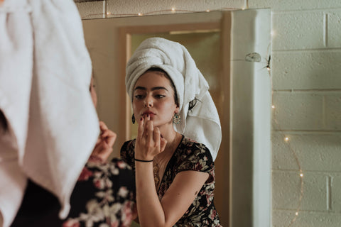 woman with hair wrapped in towel applying skincare in mirror