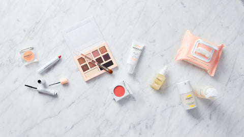 clean beauty products scattered on marble surface (honest beauty)