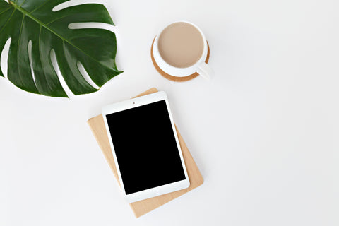 ipad and coffee next to plant leaf on white background