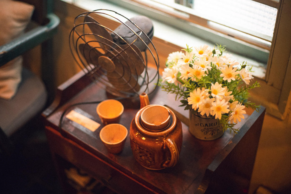 night stand with fan, vase with daisies and teapot with two teacups