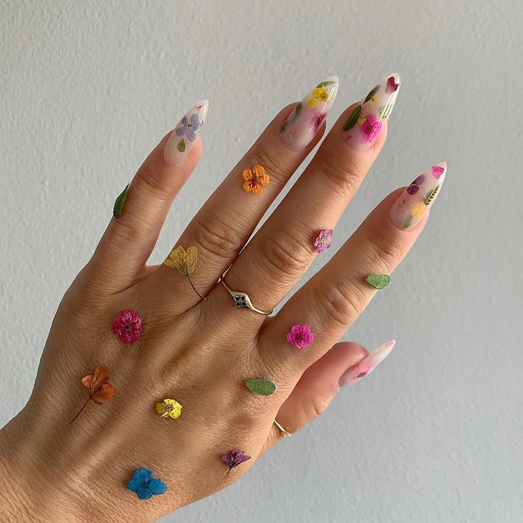 Hand with flowers all over to showcase nail art.