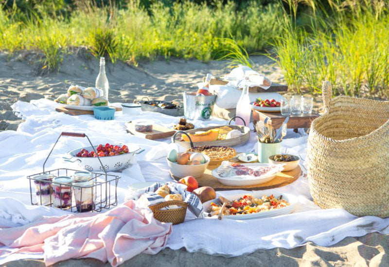 Beachside picnic, with food set out on blankets