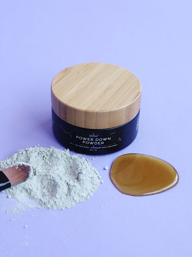 Moonlit Skincare's Power Down Powder with the mask ingredients laying in front of the  container.