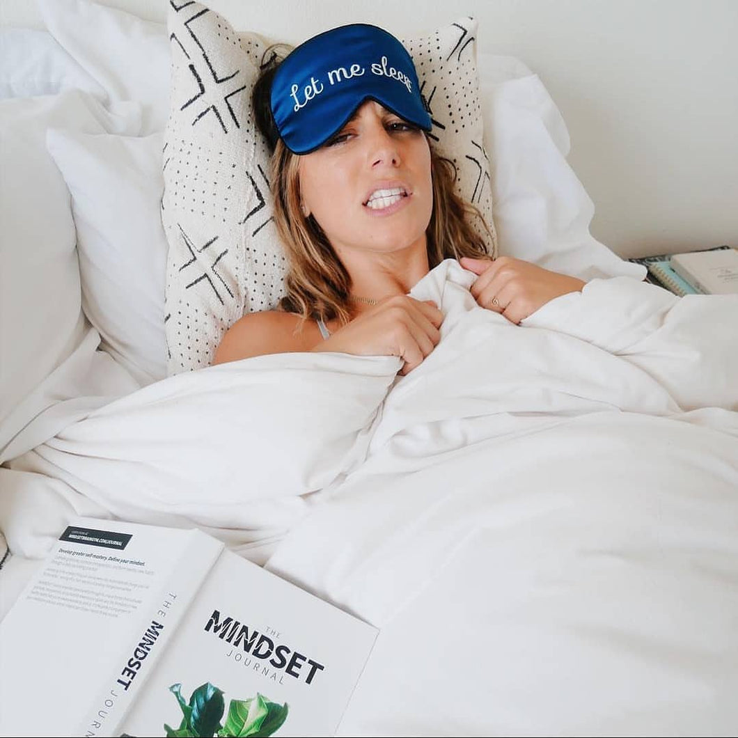 Woman lying in bed with a Let Me Sleep Silk Sleeping Eye Mask pushed up to her forehead and a book by her side